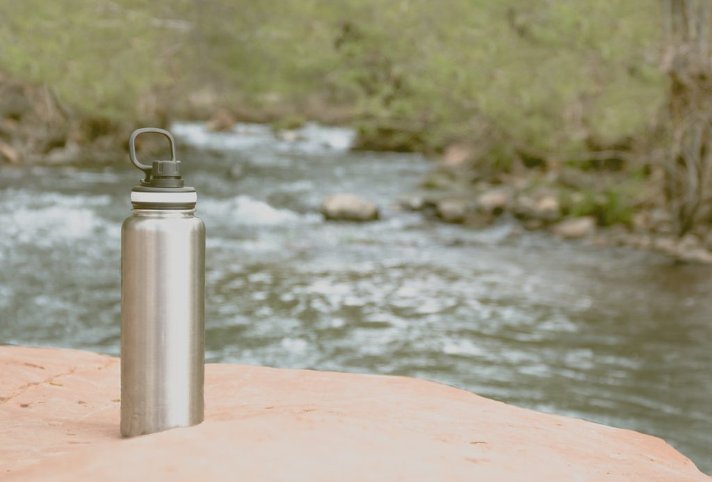Silver filtered water bottle on sand near a stream