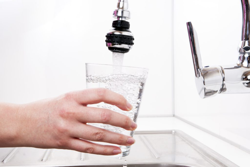 Person filling glass from faucet-mounted water filter